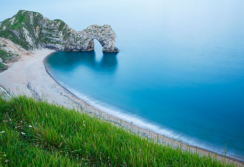Evening view of Durdle Door beach, Dorset, England. Durdle door is one of the many stunning locations to visit on the Jurassic coast in southern England. Adventures in Britain - UK travel guide